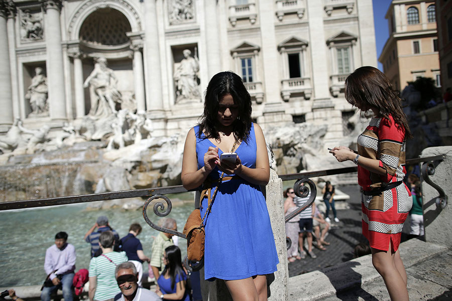 Women use smartphones in front of the Trevi Fountain in Rome September 20, 2012. Italy has long been an Internet laggard, its creaky networks stunting the development of online commerce and banking. Italians pay among the highest prices in Europe for broadband speeds on a par with Estonia or Cyprus. As a result, only half the population uses the Internet at least once a week and Italian firms generate 5.4 percent of sales on-line compared to 13.9 percent elsewhere in Europe. Now the reformist government of Prime Minister Mario Monti has identified better broadband as a national priority to spur growth and reduce Italy's 11 percent unemployment and bulging deficits. Picture taken September 20, 2012. To match Insight ITALY/BROADBAND REUTERS/Tony Gentile (ITALY - Tags: BUSINESS TELECOMS TRAVEL SOCIETY) - RTR38FDO